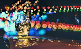 Abstract bokeh of festive lights through a glass jar at twilight Stock Photo