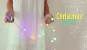 Abstract and bokeh image of young woman holding garland christmas lights and typography: CHRISTMAS PARTY. Holiday invitation conce royalty free stock photography