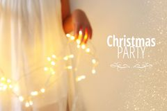 Abstract and bokeh image of young woman holding garland christmas lights and typography: CHRISTMAS PARTY. Holiday invitation conce. Pt Royalty Free Stock Image