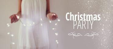 Abstract and bokeh image of young woman holding garland christmas lights and typography: CHRISTMAS PARTY. Holiday invitation conce. Pt Stock Image