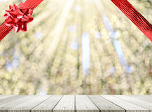 Abstract bokeh light background with red ribbon and wooden tabletop Royalty Free Stock Images