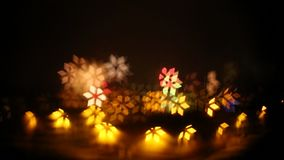 An abstract, bokeh-style video of city lights with a distant fireworks. Turning, dynamic light shapes. New Year celebration stock footage
