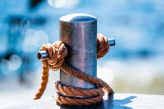 Abstract: Bollard and rope. Abstract: Rope tied in a knot on a bollard. Mooring rope wrapped around the cleat on sea background. Metallic capstan in harbor for stock photography