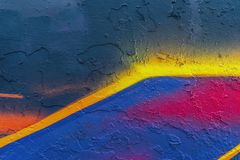 Abstract bright fragment of wall with old chipped paint, scratch, grunge texture. Aerosol design, yellow, blue, pink Stock Photos