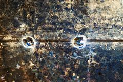 Abstract brutal background. Aged metal surface with a welded seam in the middle and two steel rivets.  stock photos