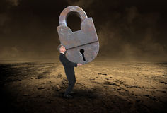 Abstract Business Concept, Lock, Security. A businessman carries a giant vintage antique metal lock. The man has a lock on business, sales, marketing, security Stock Photo
