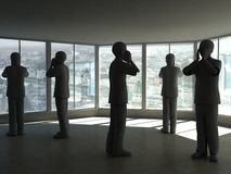Abstract business office. A view of several silhouetted businesspeople standing in an unfurnished room, appearing to be talking on telephones Stock Photography