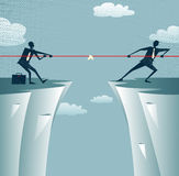 Abstract Businessmen Tug of war on a cliff. Royalty Free Stock Images