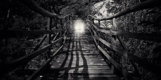 Abstract bw wooden bridge. Abstract spooky  wooden bridge with man silhouette in black and white Royalty Free Stock Photos