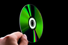 Abstract cd dvd blue-ray disk in hand. Isolated on black Royalty Free Stock Photography