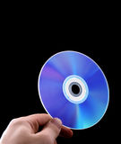 Abstract cd dvd blue-ray disk in hand. Isolated on black Stock Images