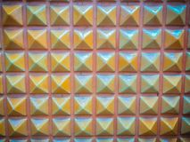 Abstract ceramic wall tiles in the shape of pyramid background. Royalty Free Stock Image