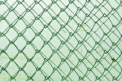 Abstract chain link fence texture against grungy color wall. Stock Images