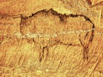Abstract children art in sandstone cave. Black carbon paint of bison on sandstone wall Royalty Free Stock Images