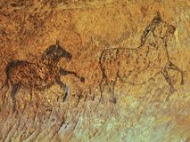 Abstract children art in sandstone cave. Black carbon paint of horses Royalty Free Stock Photography