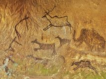 Abstract children art in sandstone cave. Black carbon paint of human hunting on sandstone wall Royalty Free Stock Images