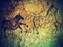 Abstract children art in sandstone cave. Black carbon paint of human hunting on sandstone wall, copy of prehistoric picture. Stock Images