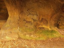 Abstract children art in sandstone cave. Black carbon paint of human hunting Stock Images