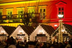 Abstract Christmas background. Crowded Christmas market in city center, decorated wooden huts with glowing lights. People enjoying event and searching for gifts royalty free stock photos