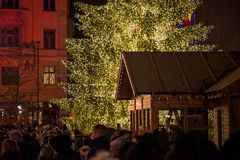 Abstract Christmas background. Crowded Christmas market in city center. Decorated Christmas tree with glowing lights and wooden huts full with gifts. Beautiful royalty free stock photography