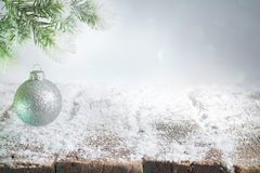 Abstract christmas background with silver bauble on fir and empty snowy table stock photos