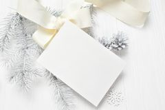 Abstract christmas background, white sheet of paper lying among small decorations on white wooden desk. Flat lay mockup for your a stock image