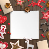 Abstract christmas background, white sheet of paper lying among small scandinavian styled decorations on wooden desk Stock Photo