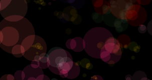 Abstract christmas colorful particles bokeh flowing on black background, holiday xmas festive stock video footage