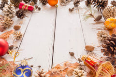 Abstract Christmas frame with cones, pine bark, acorns, and toys. White wooden background. Stock Images