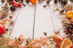 Abstract Christmas frame with cones, pine bark, acorns, and toys. White wooden background. Stock Image