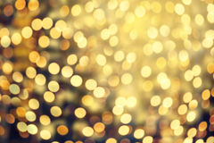 Abstract Christmas glitter vintage lights background. Dark Gold. Glitter defocused wallpaper with sparkling bokeh Stock Image