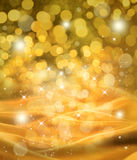 Abstract Christmas Gold Satin Background. A gold satin abstract Christmas background with star lights and bokeh Stock Photography