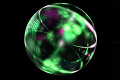Abstract Christmas green ball on black background Stock Photos