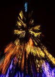 Abstract Christmas lights background at night. Christmas tree blurred with zoom effect Stock Image