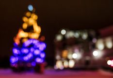 Abstract Christmas lights background at night. Christmas tree on the city square blurred with bokeh effect Stock Image