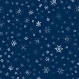 Abstract Christmas seamless pattern from white snowflakes on a blue background. For holiday, new year, celebration, party. Stock Photos