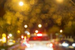 Abstract cirkelbokeh onscherp geel licht op de weg met onduidelijk beeld witte auto bij nacht Stock Afbeeldingen