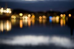 Abstract city lights at night out of focus. With reflections in water Stock Images