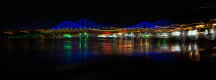 Abstract cityscape with a bridge over the river and multi-colored lights royalty free stock photos