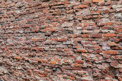 Close up of a rough brick wall with bricks on the left farther away than the right. Abstract close up of a rough brick wall with bricks on the left farther away royalty free stock photo