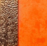 Abstract closeup view of interior orange painted wall with fragment of mirror decorated metal frame. Beautiful amazing abstract closeup view of interior orange royalty free stock image