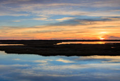 North Carolina Cloud Water Reflection Marsh Sunrise. Abstract background of white clouds and blue sky reflecting in the marsh water at sunrise on Cape Hatteras Royalty Free Stock Image