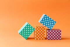 Abstract colorful geometric background vivid polka dots pattern cube boxes. Violet blue green rectangular block. Composition on orange paper background. Shallow royalty free stock image