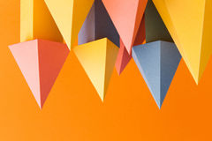 Abstract colorful geometrical shapes background. Three-dimensional prism pyramid objects on orange paper. Yellow blue. Pink green colored solid figures, soft royalty free stock photography