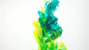 Abstract colourful clouds of ink moving in water, white background. Yellow, green acrylic paint swirling in water. Traces of ink dissolving in water ever stock video footage