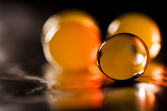 Abstract composition with beautiful, orange, transparent, round jelly balls on an aluminium foil with reflexions Stock Image