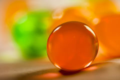 Abstract composition with beautiful, orange, transparent, round jelly balls on an aluminium foil with reflexions Royalty Free Stock Photography