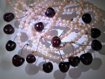 Abstract composition of berries and cherry pearl white and pink necklaces. Abstract cherry berries and pearl white and pink necklaces - elegant, glamorous and Stock Photos