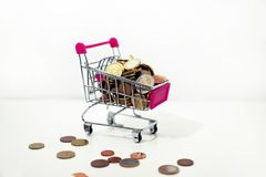 Small cart with coins isolated on white background. Abstract composition of buying something. Small cart with coins isolated on white background royalty free stock photography