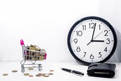 Small cart with coins on white background. Abstract composition of buying something. Small cart with coins on white background stock image